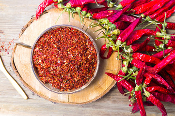 Ground and whole peppers on rustic wooden table