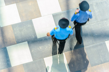 Two Policemen Patrolling the Area, Top View. Silhouettes of Two Police Officers in Blue Uniform. Abstract Background. Motion Blur. Long Exposure