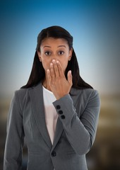 Businesswoman covering mouth with hand in city