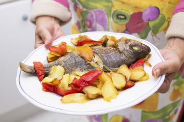 hands with roasted fish dish with potatoes and peppers