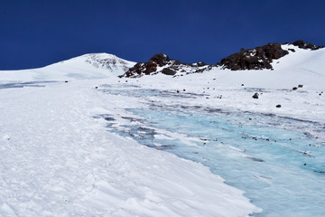 glacier among the rocky mountains. blue sky in the background. snow-capped peaks of the ridge