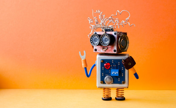 Friendly crazy robot handyman on orange background. Creative design cyborg toy. Copy space photo