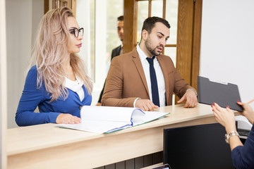 Beautiful business lady with her blonde secretary in the waiting area of an office talking and explaining her something on a folder full with documents