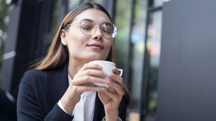 Young beautiful woman drinking coffee or tea