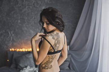 Bare back girl with a huge tattoo standing on the background lights garlan