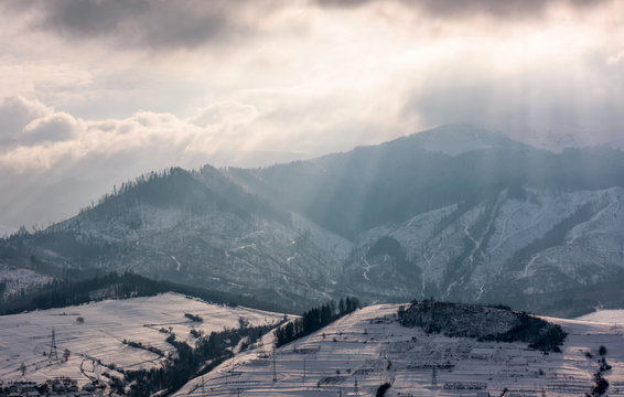 sunbeams through clouds over the snowy mountains. beautiful countryside scenery in winter