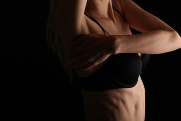 Beautiful female athlete body , perfect abdominal muscles and obliques. Strong sport woman on black background, low key image