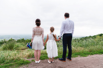 young married couple and their little daughter on wedding day are standing in nature holding hands