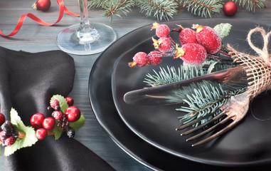 Black plates and cutlery with Christmas decorations on dark, close-up