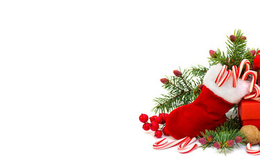 Christmas decoration with christmas stocking, branch of spruce, candies, walnut, berry, gift box on white background with space for text