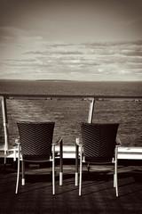Ausblick und zwei Stühle auf dem Deck eines Schiffes, monochrom