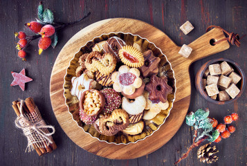 Plate of Christmas cookies on a wooden board on dark rustic background