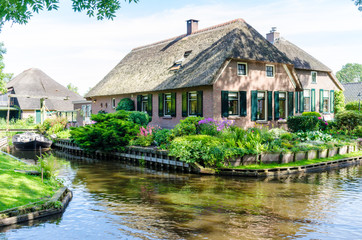 "Giethoorn, Netherlands: View of famous Giethoorn village with canals and rustic thatched roof houses.The beautiful houses and gardening city is know as ""Venice of the North""."