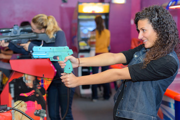 Woman firing gun on arcade game