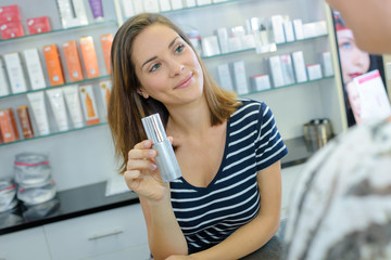 happy girl buying cosmetical cream in the shopping mall