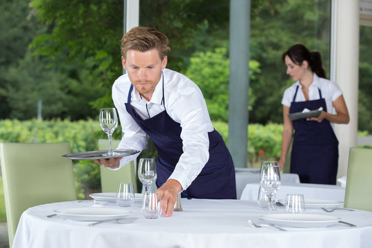 male waiter setting wedding table