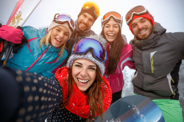 Group of friends having fun on the snow and making selfie