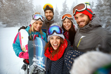 Poster Winter sports winter, extreme sport and people concept - friends having fun on the snow and making selfie