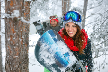 friends snowboarder having fun in the winter forest