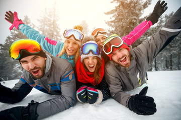 Group of friends on winter holidays - Skiers lying on snow and having fun