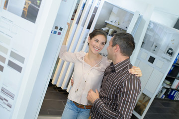 happy couple of adults choosing ceramic tile for bathroom