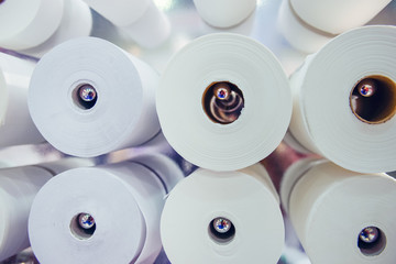 White cleaning paper rolls in several rows. Sanitation and cleaning concept background. Selective focus