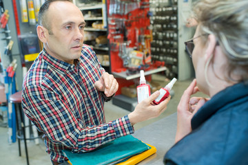 concentrated man customer choosing sealant tube in housewares hypermarket