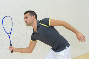 young man playing tennis indoors