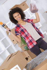 beautiful young happy woman unpacking in new home