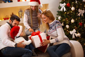 Parents giving Christmas gift to son