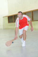 Sportsman reaching for ball with wooden racket