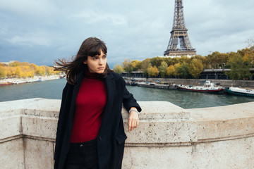 Elegant woman in black fashion coat standing in a park with Eiffel Tower on the background