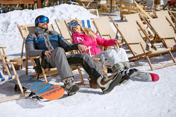 Male and female skiers enjoy in sun loungers