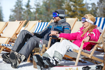 Couple in love resting from skiing in sun lounger