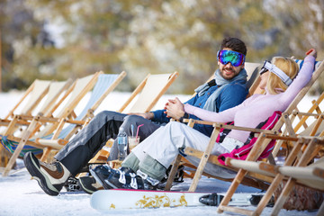 Couple enjoy in sun loungers on ski terrain