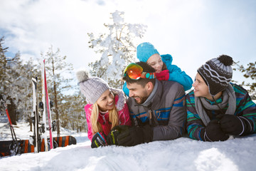 Family lying on snow at winter vacation