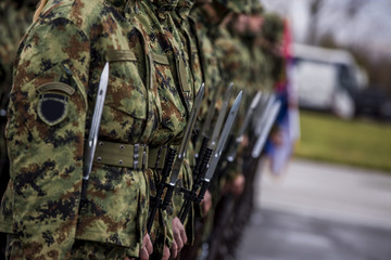 Soldiers stand in row. Gun in hand. Army, Military Boots lines of commando soldiers in camouflage uniforms
