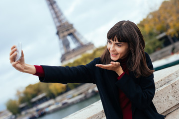 Tourist happy young woman taking selfie with smartphone and blowing air kiss near of Eiffel tower in Paris
