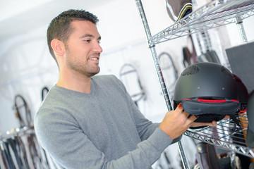 Man looking at horse riding helmet