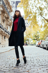Beautiful amazing brunette woman in spring or fall stylish urban outfit walking on Paris street on with Eiffel background.
