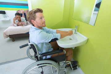 man on wheelchair washing his hands
