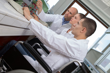young man on wheelchair and woman in laboratory