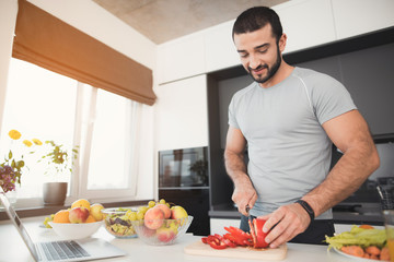 A young athletic man prepares a delicious salad of vegetables. He cuts the vegetables.