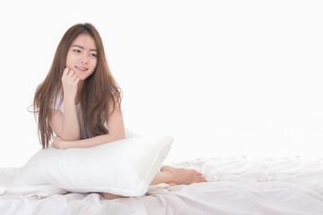 Portrait of beautiful young asian woman with braces on her teeth smiling  and sitting on white bed. Thai girl sit and smile on bed in studio white background. Free from copy space.