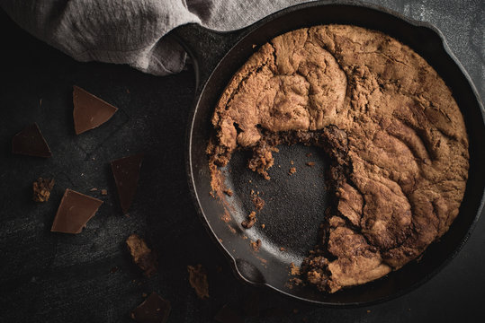Close up of chocolate chip cookie baked in a cast iron skillet.