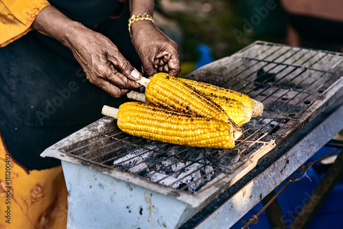 Ožld rural asian woman cooked corn cobs on the grill  Close