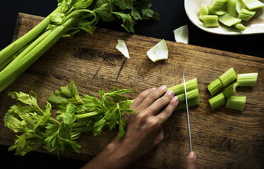 Aerial view of hands with knife cutting celery on wooden cut board