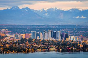 Fotomurales - Bellevue Washington. The snowy Alpine Lakes Wilderness mountain peaks rise behind the urban skyline.