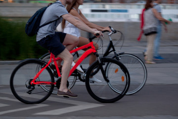 a girl and a guy spend time together riding on bicycles in the summer evening city