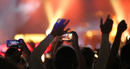 fans take photos with modern smartphones during the live concert